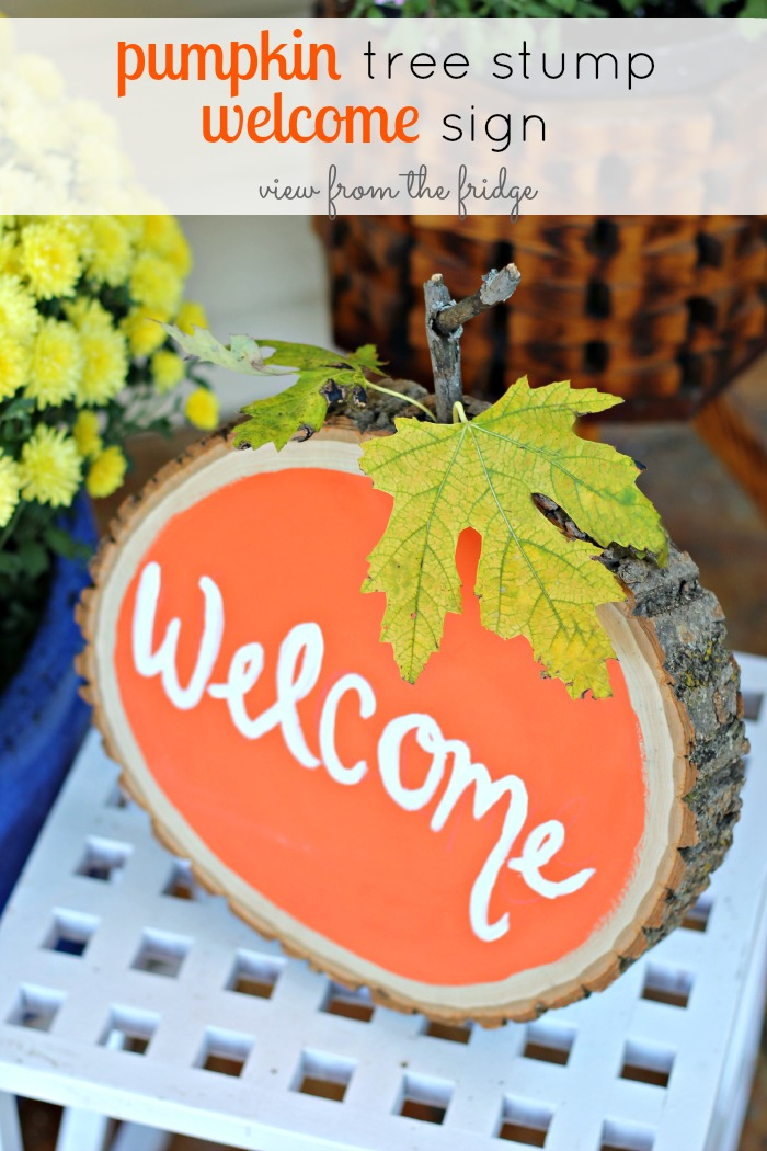 "A Friendly Pumpkin Tree Stump Sign Says ""Welcome"""