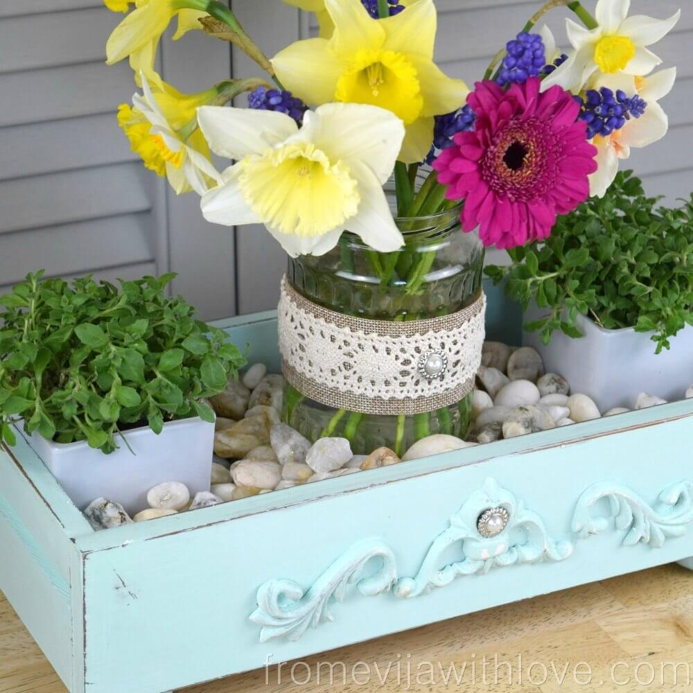 A Reclaimed Drawer with River Stones and Flowers