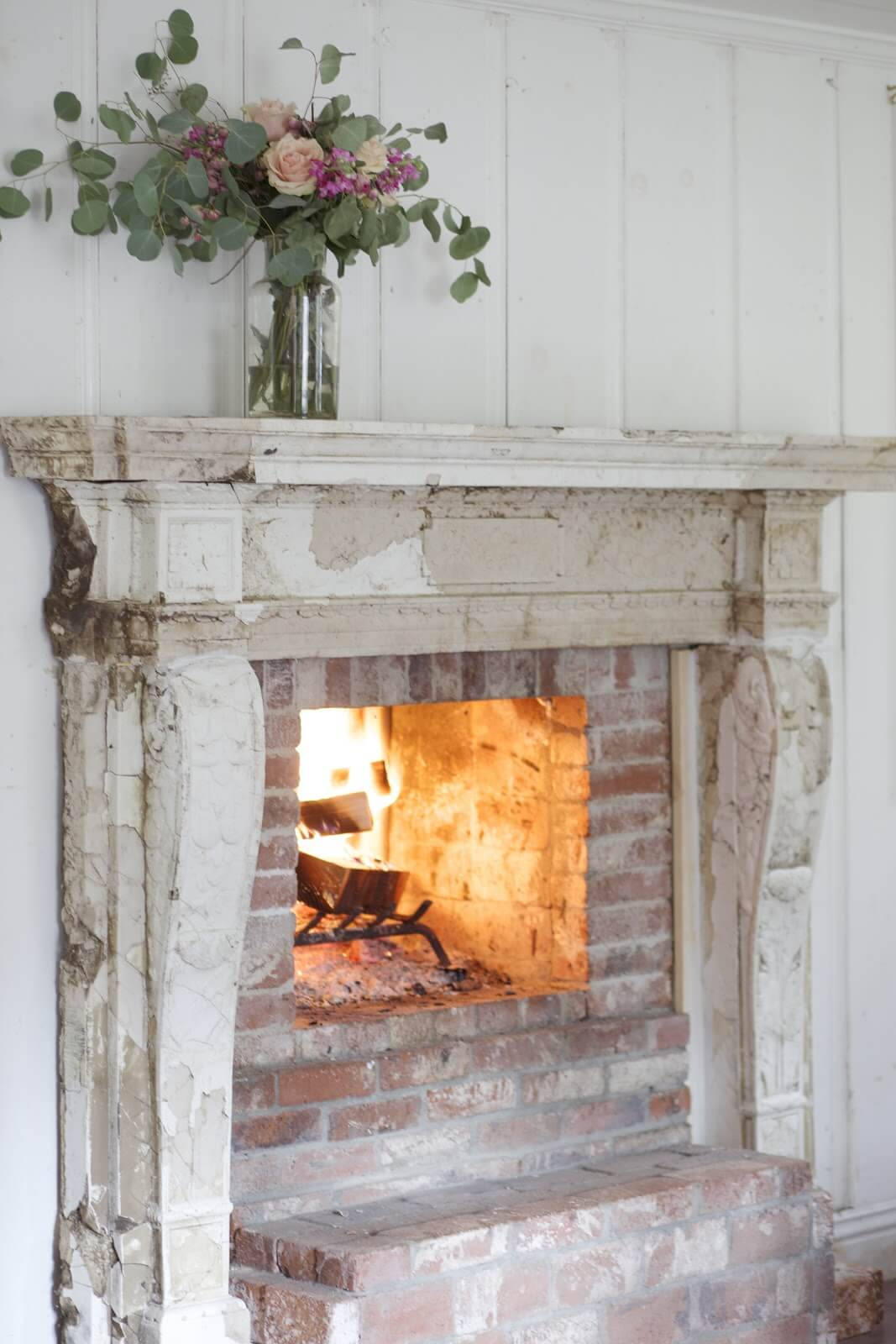 Distressed Wood Burning Fireplace with Flowers