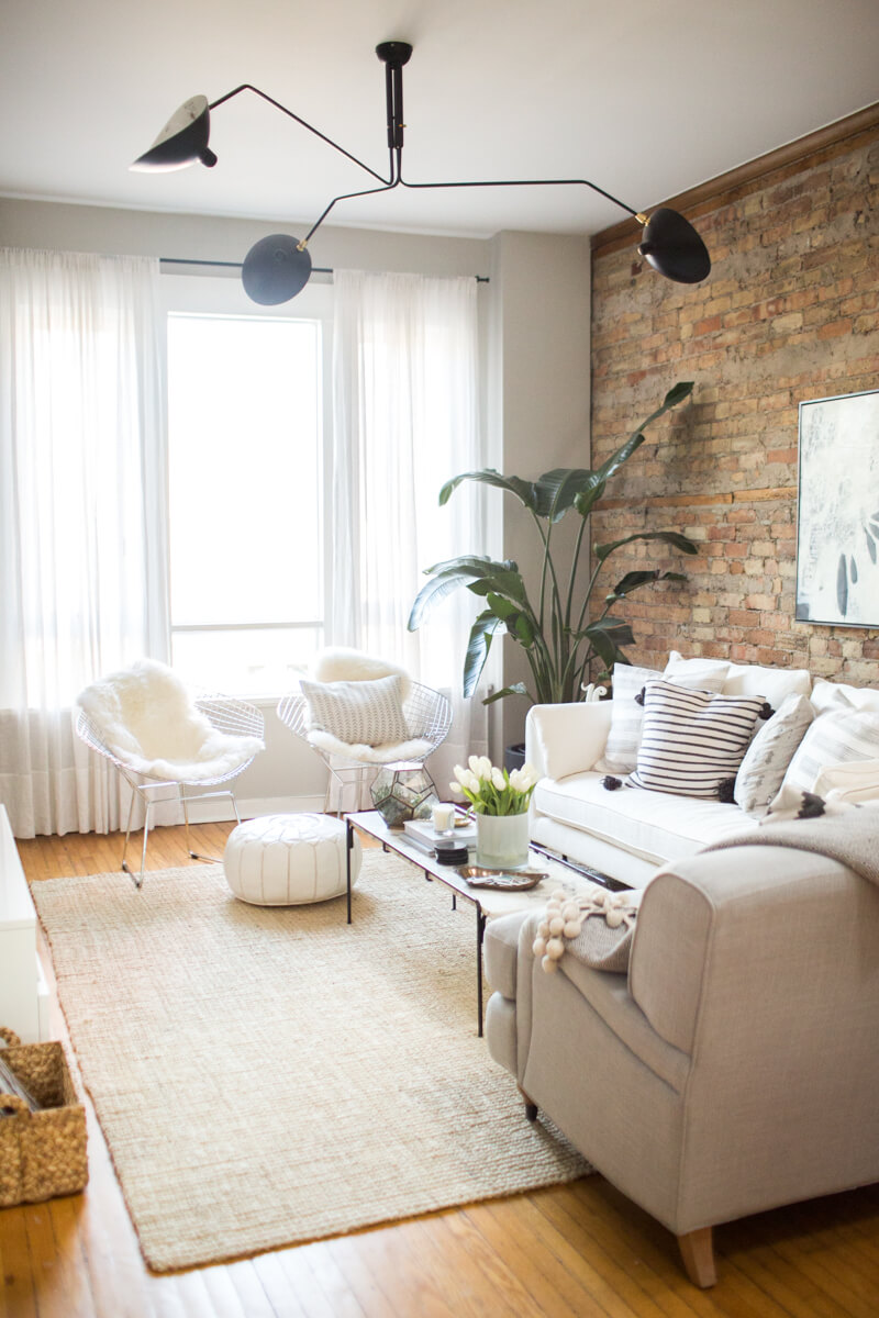 Exposed brick creamy couches and black fixtures