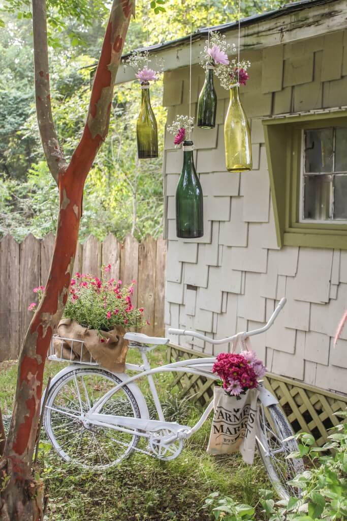 Vintage Bicycle and Flower-Filled Green Glass Bottles